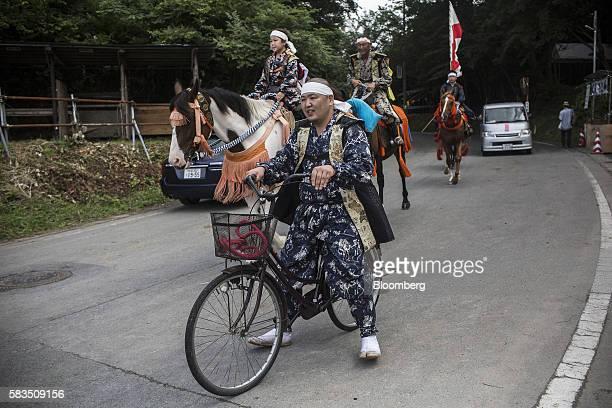 A samurai horseman rides a bicycle from the Soma Nomaoi festival in Minamisoma Fukushima Prefecture Japan on Sunday July 24 2016 Every July hundreds...