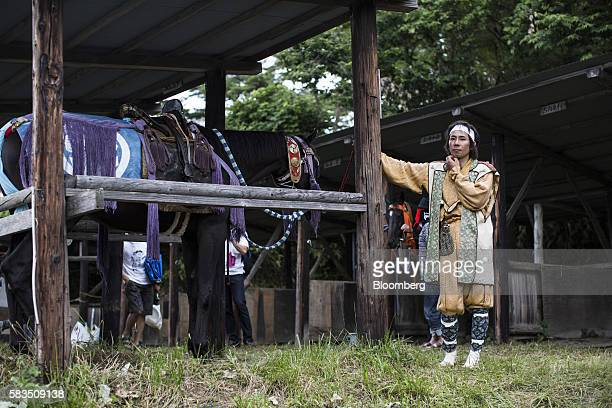 Samurai horseman stands next to horses in a barn during the Soma Nomaoi festival in Minamisoma, Fukushima Prefecture, Japan, on Sunday, July 24,...