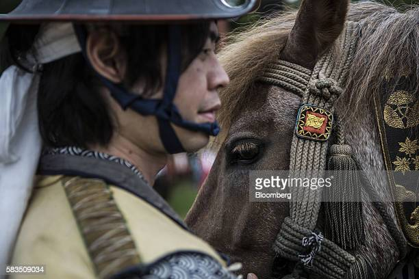Samurai horseman tends to a horse while waiting for a procession to start during the Soma Nomaoi festival at the Nakamura Shrine in Soma, Fukushima...
