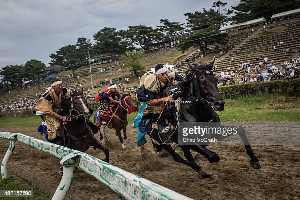 Samurai horsemen compete in the Kacchukeiba during the Soma Nomaoi festival at Hibarigahara field on July 25 2015 in Minamisoma Japan Every summer...
