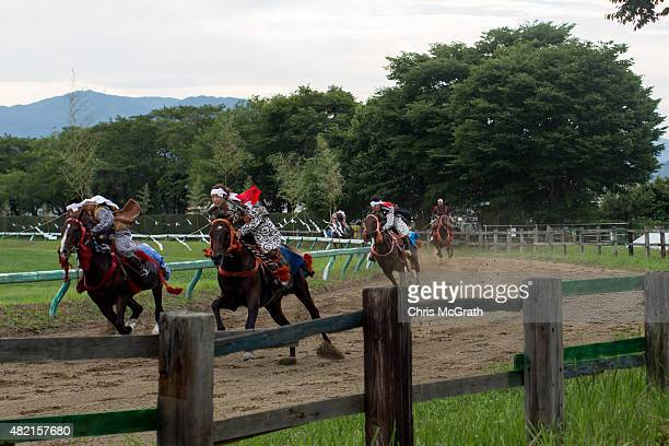 Samurai horsemen compete in the Kacchu-keiba during the Soma Nomaoi festival at Hibarigahara field on July 25, 2015 in Minamisoma, Japan. Every...