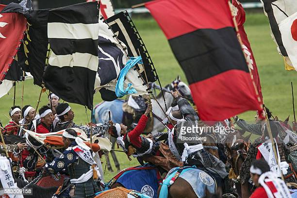 Samurai horsemen fight for a flag in the Shinkisoudatsusen sacred flag competition during the Soma Nomaoi festival at Hibarigahara field in...