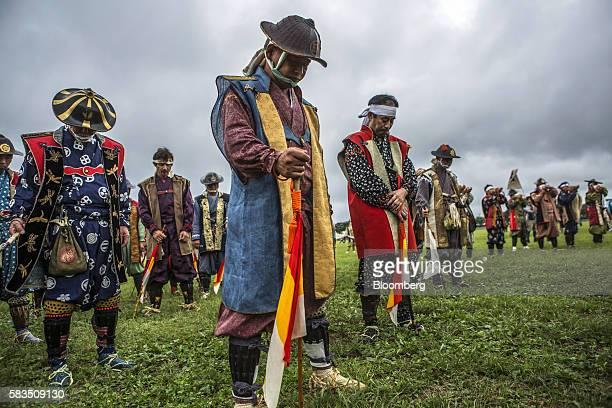 Samurai horsemen pray in a ceremony during the Soma Nomaoi festival at Hibarigahara field in Minamisoma Fukushima Prefecture Japan on Sunday July 24...
