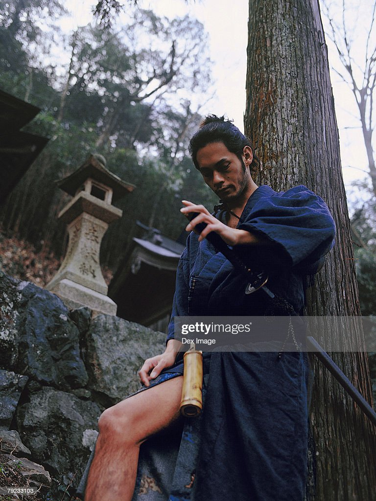 Samurai warrior leaning against a tree : Stock Photo