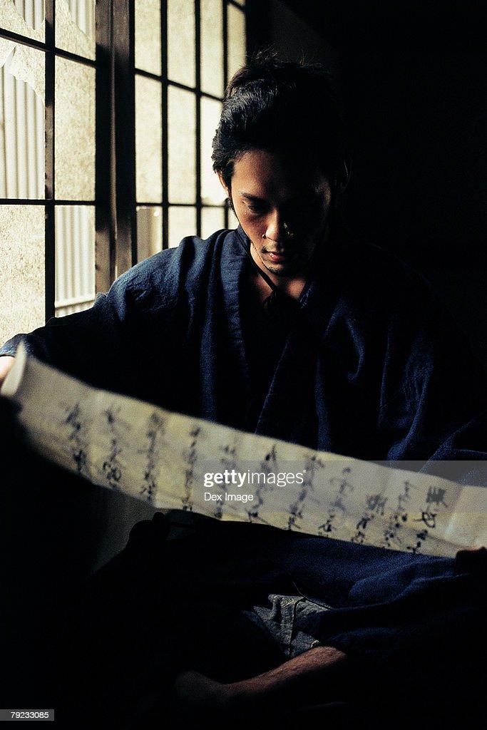Samurai warrior reading a Japanese document : Stock Photo