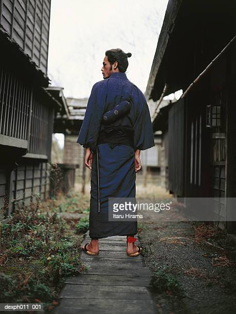 Samurai warrior standing between two rows of houses