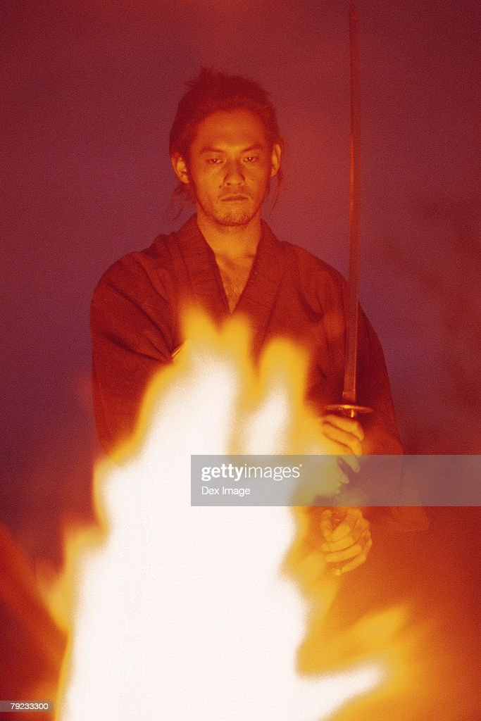 Samurai warrior standing in front of burning fire : Stock Photo