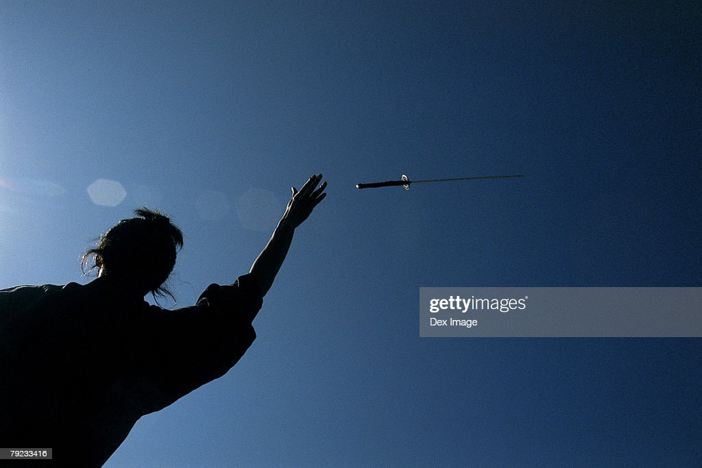 Samurai warrior throws a sword in the air : Stock Photo