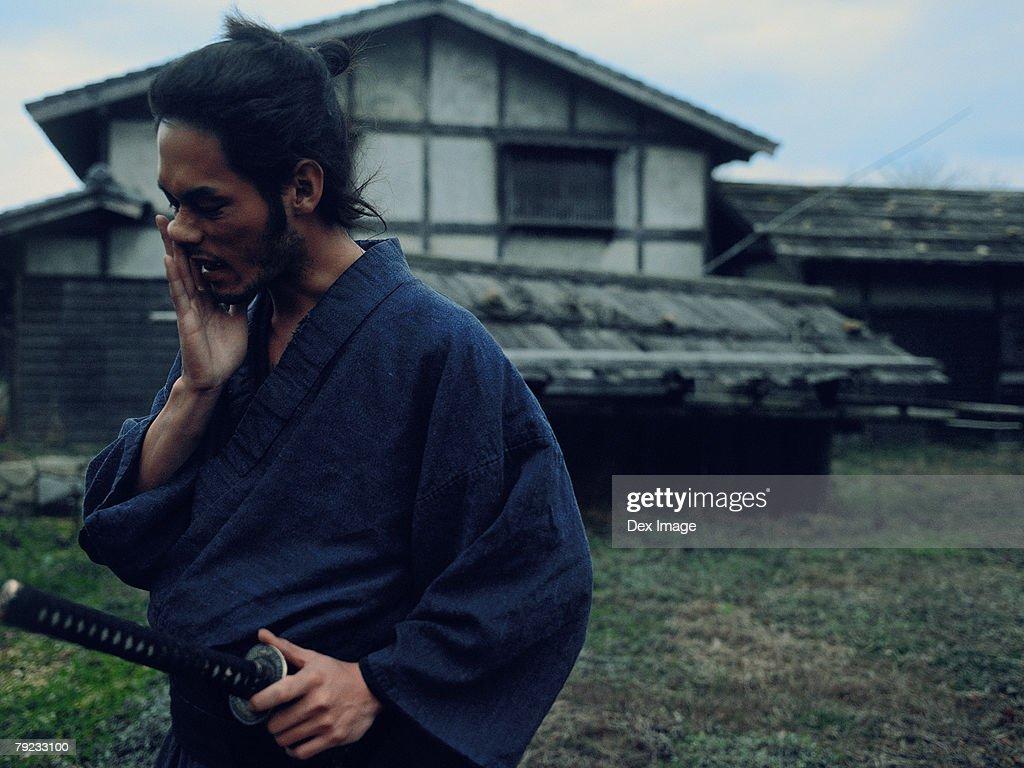 Samurai warrior walking in a village holding a sword : Stock Photo