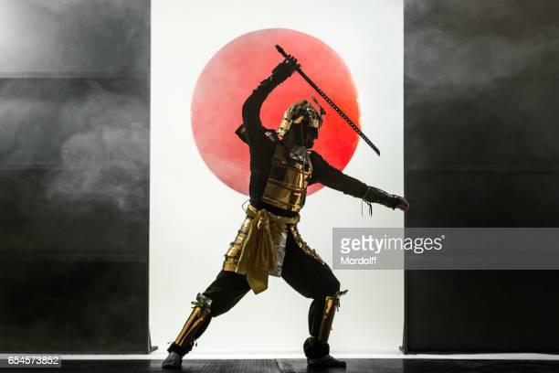 昇る太陽の背景に刀と侍