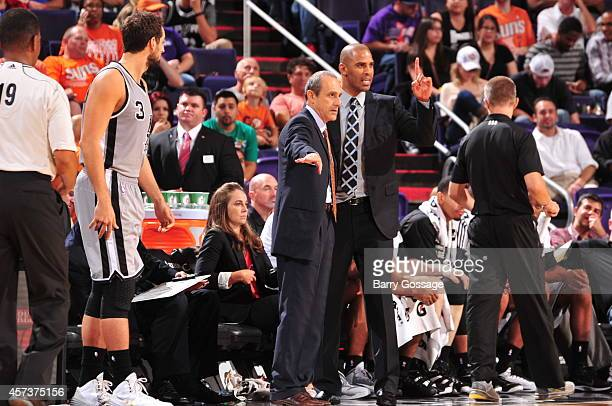 San Antonio coaches Ime Odoka and Ettore Messina talk during a preseason game against the Phoenix Suns on October 16 2014 at US Airways Center in...