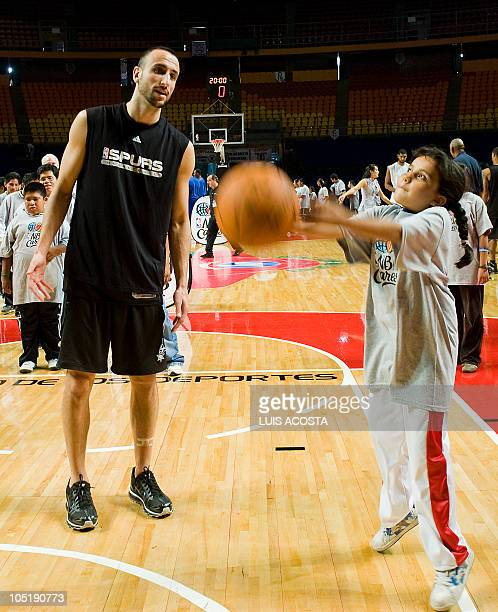 San Antonio player Manu Ginobili plays with a child affected by the Down syndrome during a NBA basketball clinic held after a training session in...