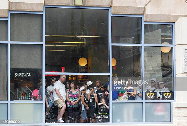 San Antonio Spur fans watch from the River Center Mall during the victory parade down the Riverwalk on June 18 2014 in San Antonio Texas NOTE TO USER...