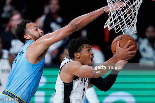 San Antonio Spurs' Keldon Johnson shoots around Memphis Grizzlies' Kyle Anderson during the first half of an NBA basketball game at Visa Athletic...