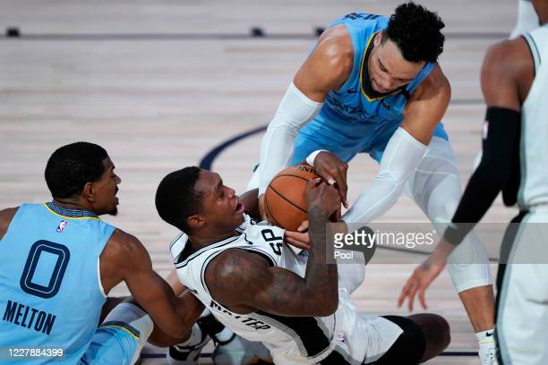 San Antonio Spurs' Lonnie Walker IV, center, scrambles for the ball with Memphis Grizzlies' De'Anthony Melton, left, and Dillon Brooks, right, during...