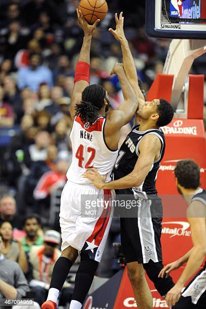 San Antonio Spurs power forward Tim Duncan tries to block the shot of Washington Wizards power forward Nene Hilario during the second half at the...