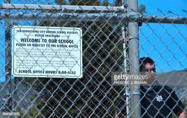 A San Bernardino police officer mans his position at a closedoff North Park Elementary School in San Bernardino California on April 10 following a...