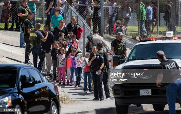 San Bernardino Police officers help evacuate children to awaiting school buses after a shooting inside North Park Elementary School on April 10 2017...
