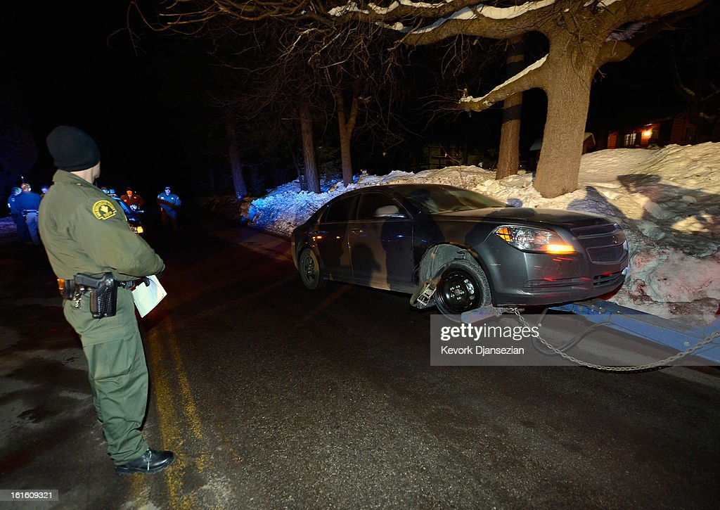A San Bernardino Sheriff's Department deputy watches as a car is towed away after a standoff and a shootout with former Los Angeles Police Department officer Christopher Dorner who is suspected of triple murder on February 12, 2013 in Angelus Oaks, California. Dorner barricaded himself in a cabin near Big Bear, California which later caught fire. According to the LAPD the cabin remains too hot to enter and a body has not been located.