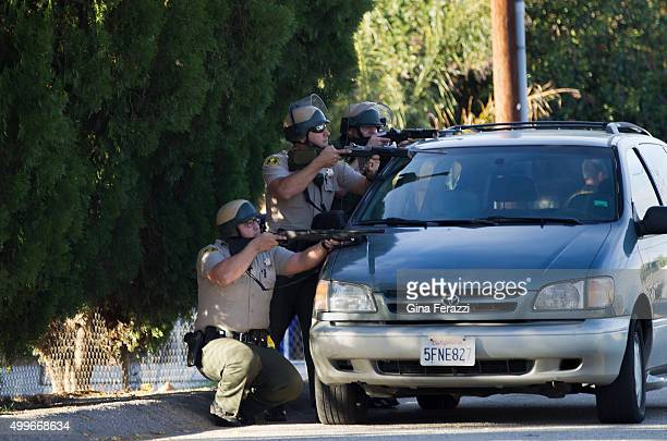 San Bernardino Sheriff's Deputies crouch behind a minivan with drawn guns on Richardson Street searching for suspects after a mass shooting at the...