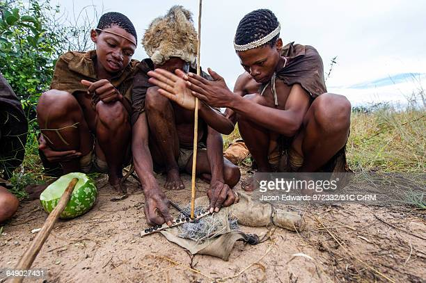 San Bushmen starting a fire using dry grass kindling, a wooden drill of hard wood and a soft wood fire board.