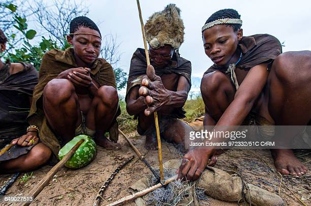 San Bushmen starting a fire using dry grass kindling a wooden drill of hard wood and a soft wood fire board