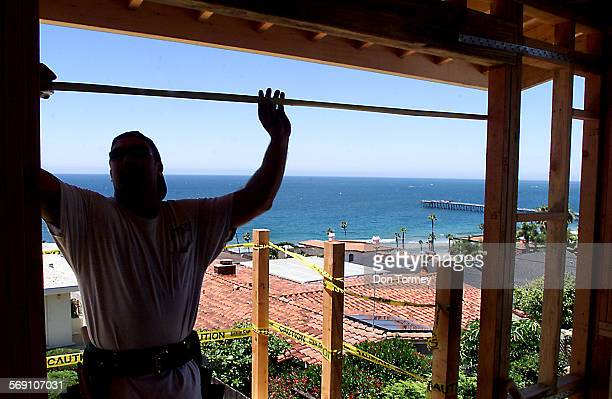 San Clemente––Frank Earnest who works for Birch Construction Company of Dana Point measures a window opening on an second story addition to a single...