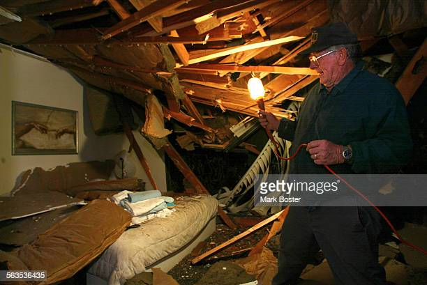 San Clemente–San Clemente resident Tom Dugin checks out the damage done to his daughter's home after a eucalyptus tree fell across the roof from high...
