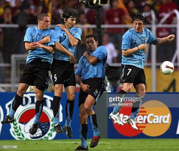 Uruguay's footballers Diego Perez Pablo Garcia Dario Rodriguez and Cristian Rodriguez fail to stop Venezuela's Juan Arango free kick at goal 07 July...