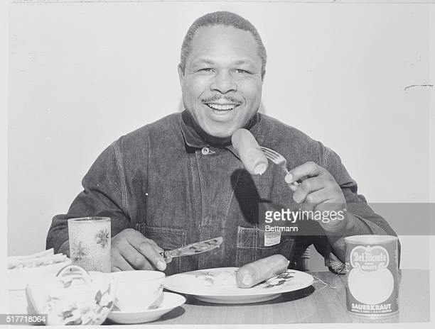Tries Teutonic Training Light heavyweight boxing champion Archie Moore stokes up on a German meal of knackwurst and sauerkraut here as he prepares...