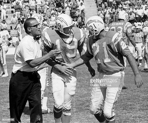 San Diego Chargers head coach Sid Gillman congratulates flanker Lance Alworth and quarterback John Hadl following a 3114 victory over the Houston...
