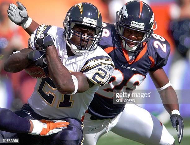 San Diego Chargers LaDainian Tomlinson scrambles with the ball as Denver Broncos Kenoy Kennedy closes in for the tackle during first quarter action...