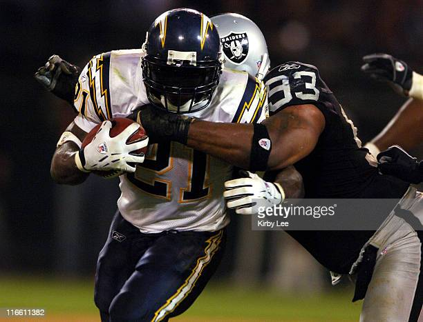 San Diego Chargers running back LaDainian Tomlinson tries to break free from grasp of Oakland Raiders defensive tackle Tommy Kelly in ESPN Monday...