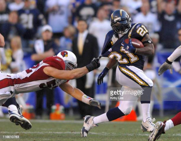 San Diego Chargers running back LaDainian Tomlinson tries to elude a jerseygrabbing tackle attempt by a diving Monty Beisel of the Arizona Cardinals...