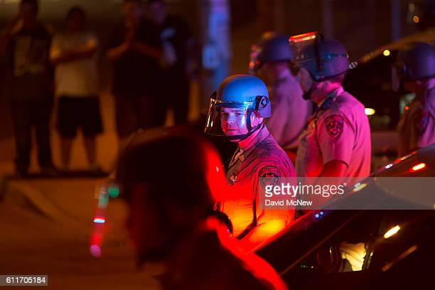 San Diego County Sheriffs deputies in riot gear watch over protesters marching in reaction to the fatal police shooting of unarmed black man Alfred...