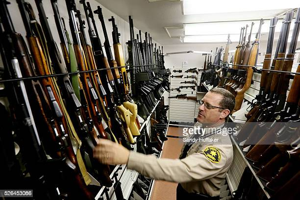 A San Diego County Sheriff's deputy looks over confiscated guns and rifles at the crime lab in San Diego CA on Tuesday March 19 2013 The weapons will...