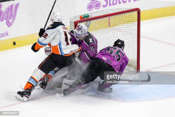 San Diego Gulls right wing Corey Tropp and Cleveland Monsters defenceman Garret Cockerill collide with Cleveland Monsters goalie Matiss Kivlenieks...