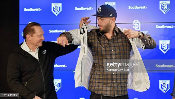 San Diego Padres' Eric Hosmer puts on his new jersey with the help of his agent Scott Boras while being introduced on Tuesday Feb 20 2018 at a press...