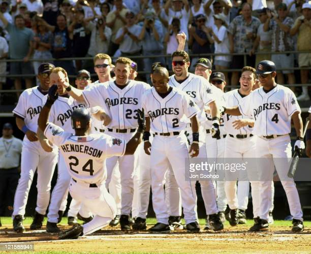 San Diego Padres gather at home plate as Rickey Henderson keeps a promise and slides in to home plate after hitting a home run for career run number...