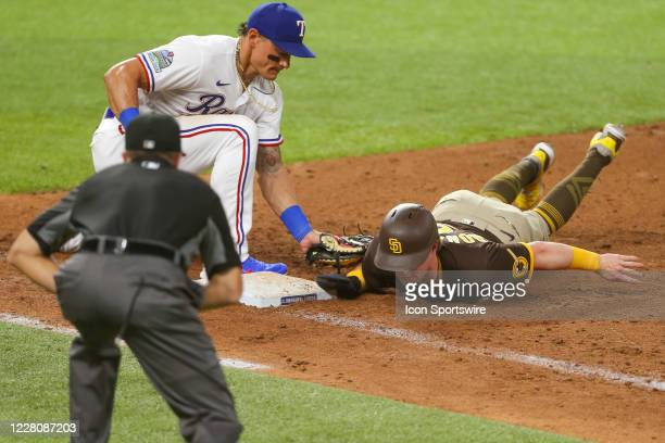 San Diego Padres second baseman Jake Cronenworth dives in just ahead of a pick off tag by Texas Rangers first baseman Derek Dietrich during the MLB...