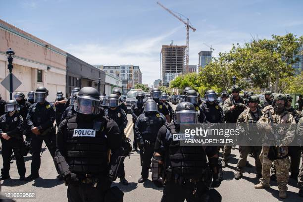 San Diego Police officers in riot gear and a special tactics group faceoff with demonstrators in downtown San Diego California on May 31 as people...