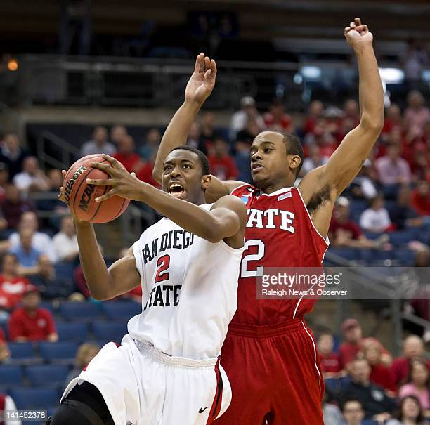 San Diego State's Xavier Thames , left, gets past North Carolina State's Lorenzo Brown , right, during the second half in the second round of the...