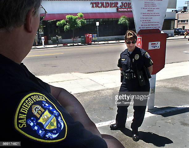 San Diego––San Diego PD Sergeant Rebecca Bigbie keeps an eye on a small protest with her partner across the street from Trader Joe's market on Garnet...