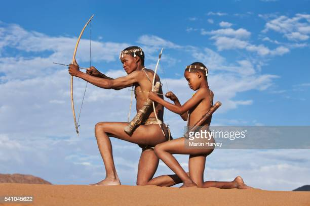 San father teaching son traditional hunting techniques