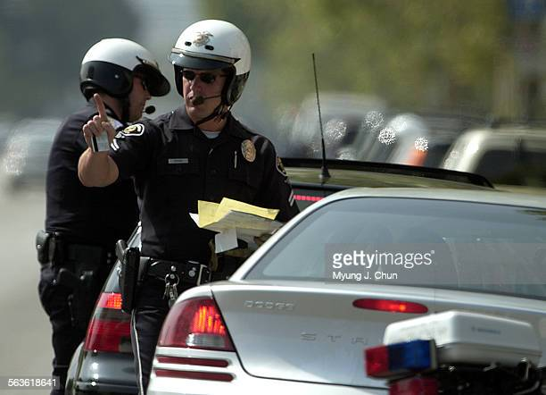 San Fernando police officer Tom Orsini explains to a motorist the right–of–way violation before issuing a citation to appear in court Wednesday...