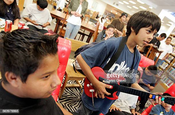 San Fernando Public Library host at least once a month video game events to attract teens after school game of choice 'Guitar Hero' Elias Ponce left...