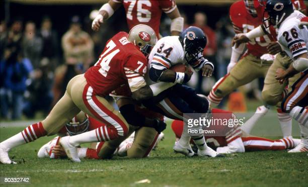 San Francisco 49ers defensive end Fred Dean wraps up Chicago Bears Hall of Fame running back Walter Payton during the 1984 NFC Championship Game a...