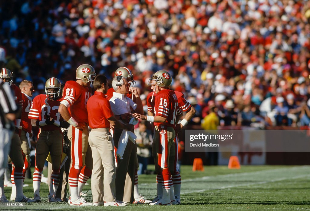 San Francisco 49ers Head Coach Bill Walsh (white shirt) confers on the sidelines with quarterback Joe Montana #16 during an NFL football game against the St Louis Cardinals played on November 9, 1986 at Candlestick Park in San Francisco, California. Other visible players include Derrick Crawford #83 and Russ Francis #81.