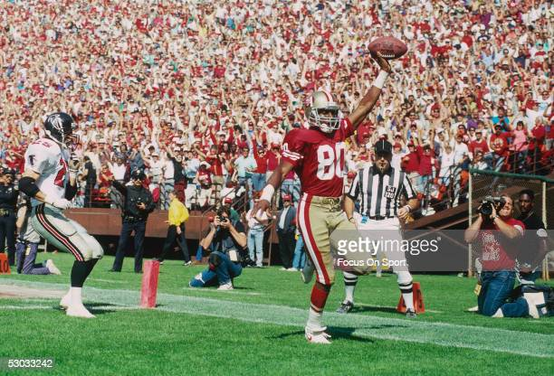 San Francisco 49ers' Jerry Rice gestures with the ball after scoring a touchdown against the Atlanta Braves during a game at Candlestick Park circa...
