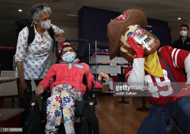 San Francisco 49ers mascot Sourdough Sam entertains Malika Kikkeri and her mother Usha Kikkeri before receiving the COVID-19 vaccine during a...